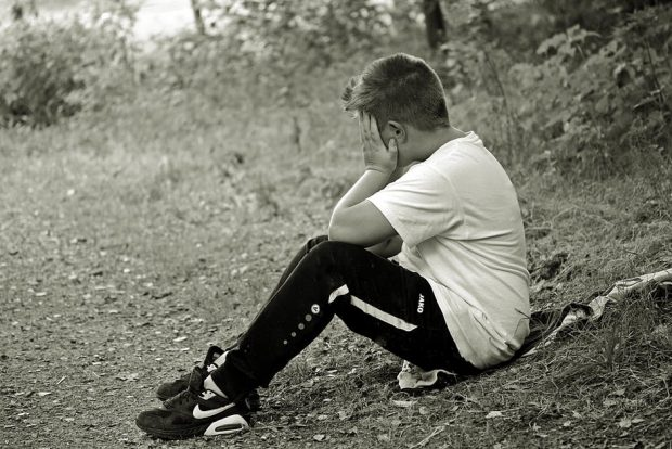 Boy sat alone with head in hands