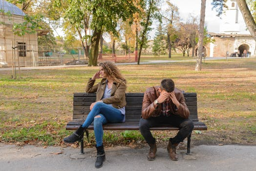 man and woman on bench. Man has head in hands and women is facing the other direction.