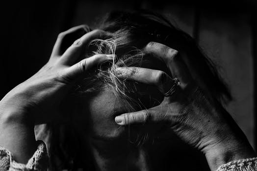 Woman with head in hands looking stressed