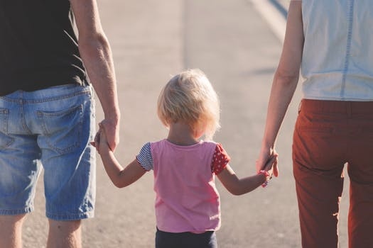 Toddler holding the hands of two adults