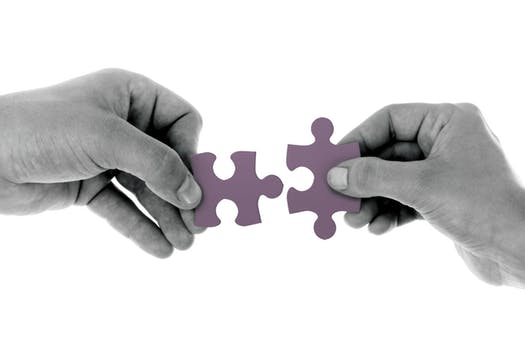 Two hands holding jigsaw pieces that fit together