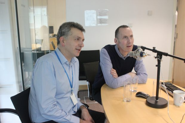 Two men sitting at a desk being videoed for a webinar session